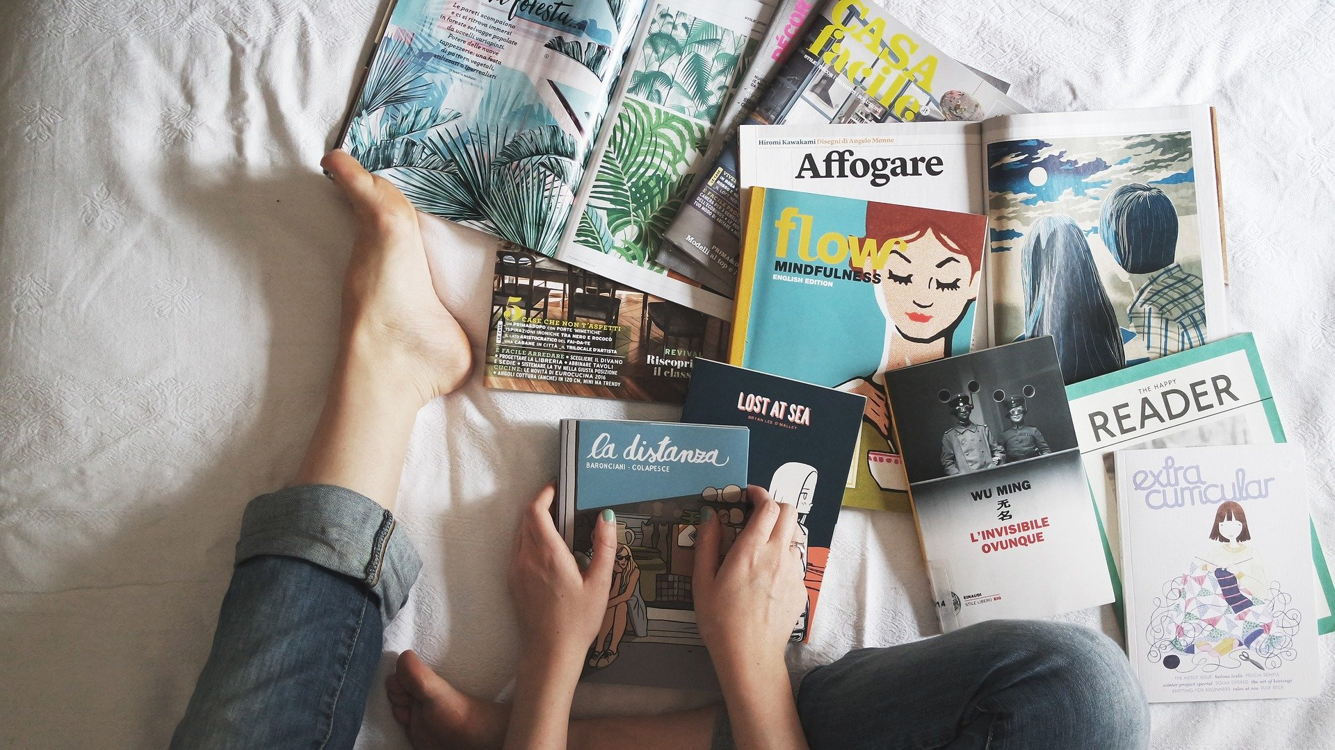 Person in bed with a pile of books and magazines at their feet.