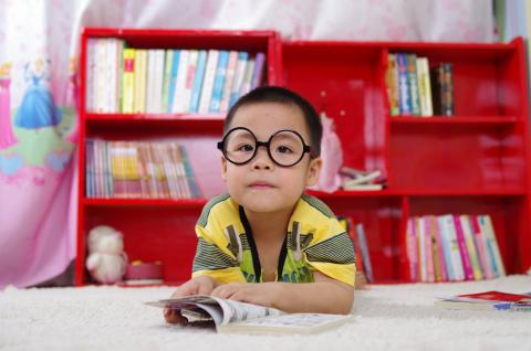 Boy reading a book with bookshelves behind him